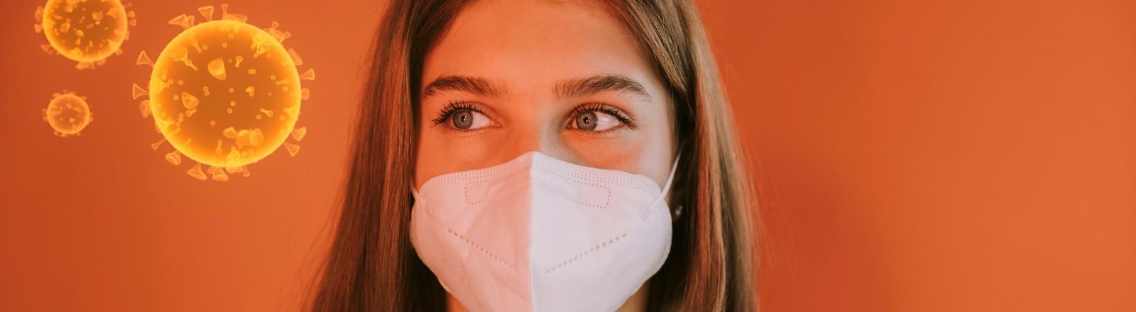 Eine Jugendliche trägt eine FFP2-Maske und schaut auf eine Grafik des Coronavirus.