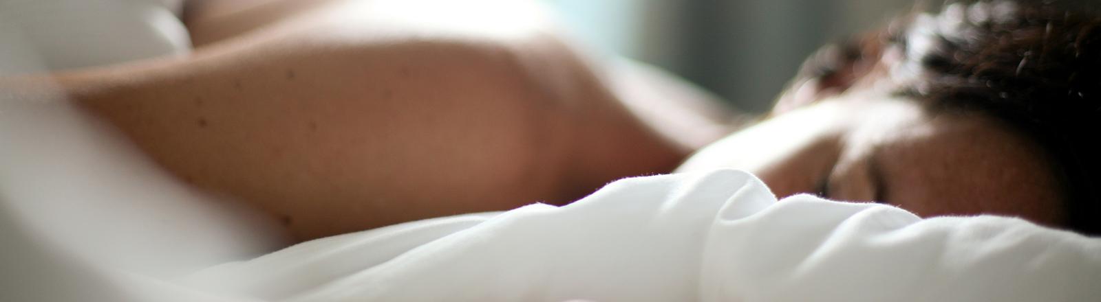 Eine Frau schläft tief und fest im Bett.