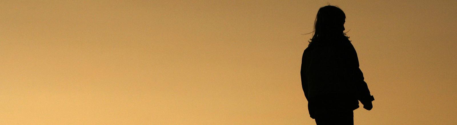 """Ein Kind steht bei Sonnenuntergang in dem Kunstwerk """"Hallenhaus""""."""