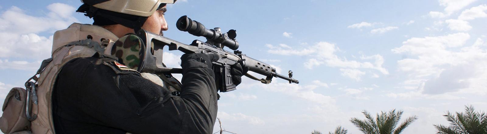 Soldat zielt mit einem Scharfschützengewehr.