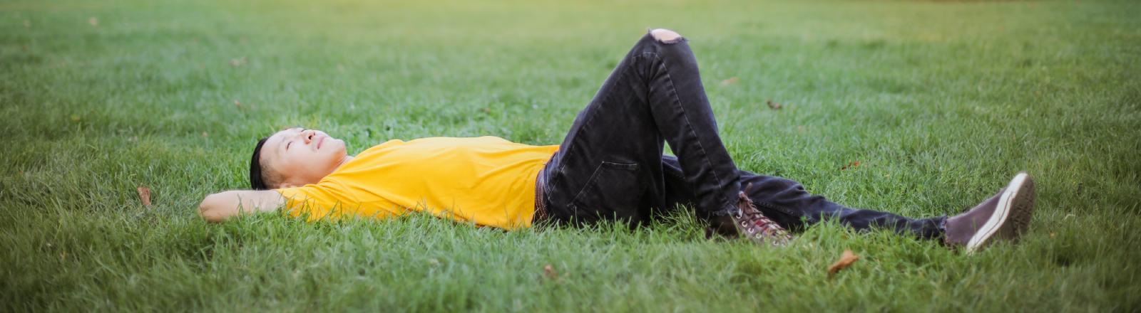 Auch der Blick in den Himmel kann Bewältigung sein: ein Mann liegt auf dem Rasen im Park