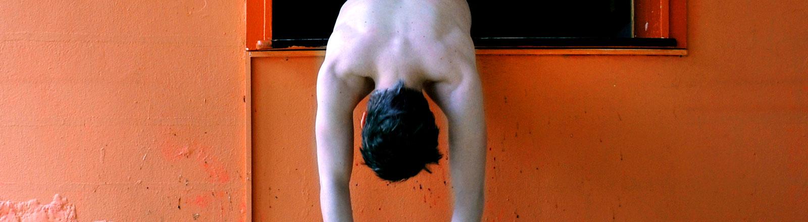 Ein Mann hängt aus einem Fenster