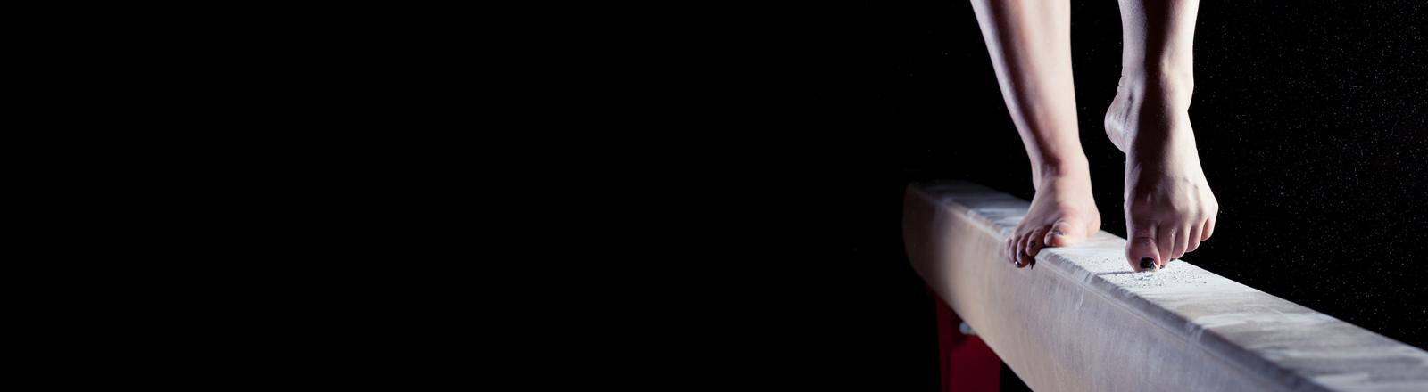 Eine Turnerin steht auf dem Schwebebalken.