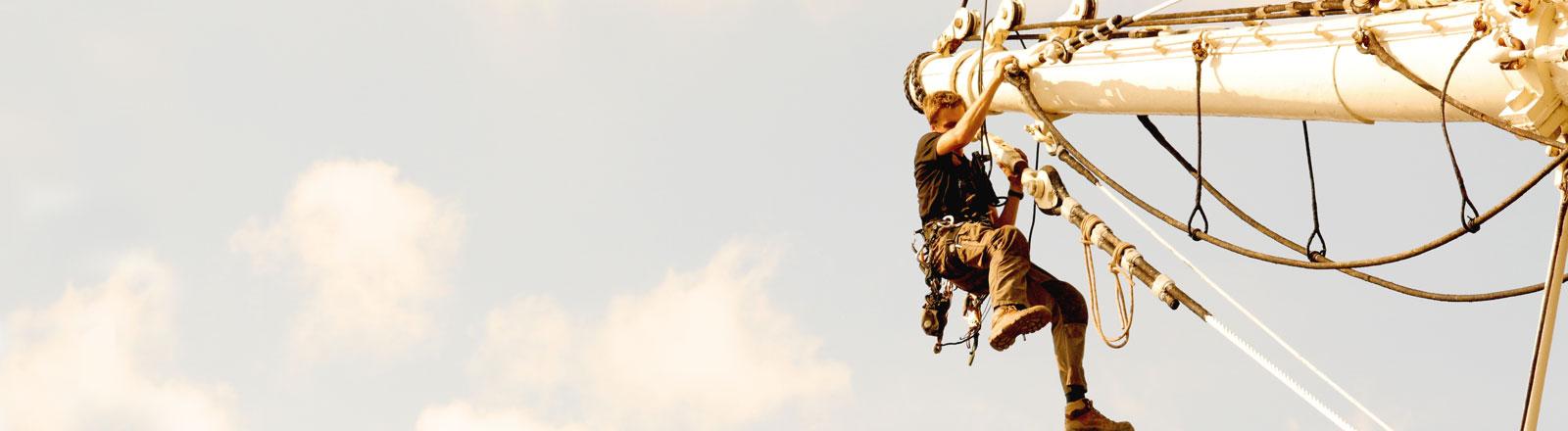 Ein Mann auf dem Mast eines Segelboots.