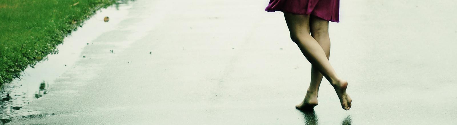 Eine Frau geht barfuß auf der Straße bei Regen.