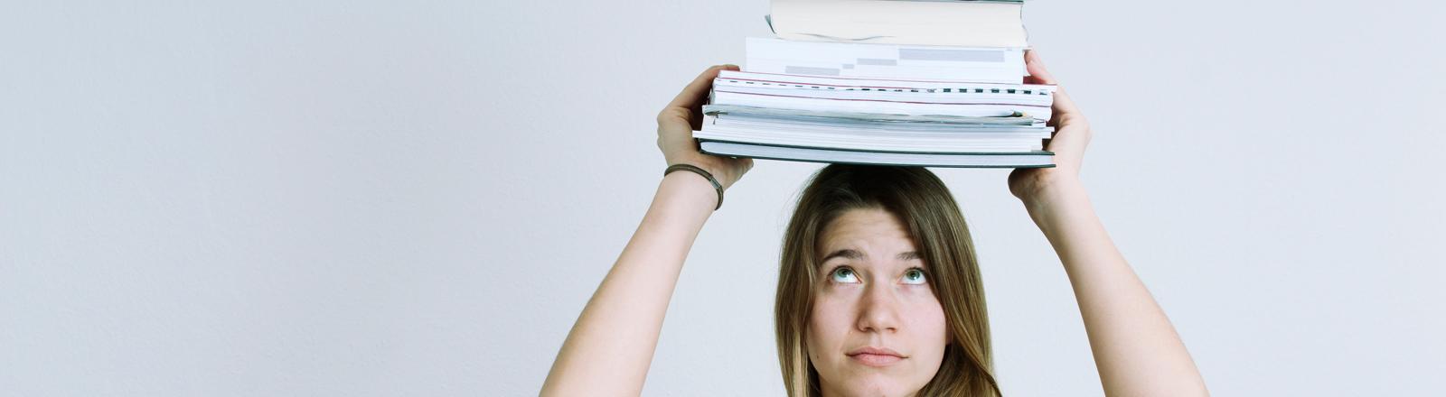 Eine Frau trägt viele Bücher auf dem Kopf.