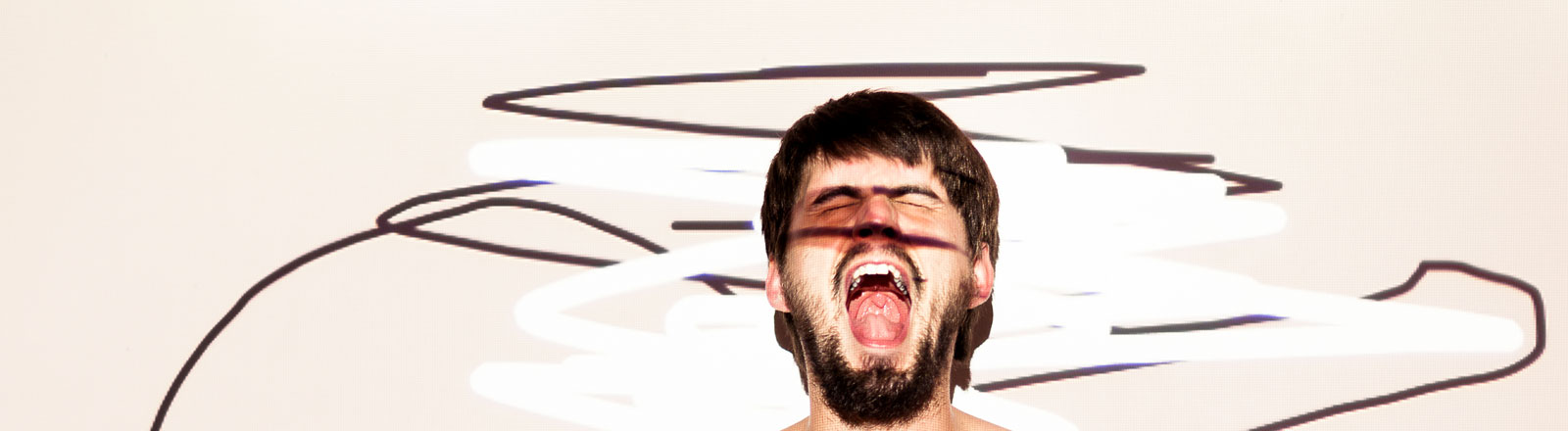 Halbnackter Mann schreit vor farbigen Hintergrund