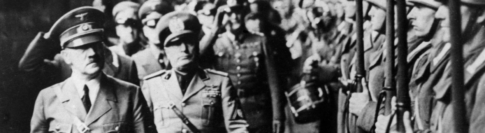 Der deutsche Diktator Adolf Hitler (l) und der italienische Diktator Benito Mussolini (rechts dahinter) inspizieren eine italienische Truppe am Brenner Pass an der deutsch-italienischen Grenze kurz vor ihrer Konferenz über die militärischen und politischen Kampagnen für den kommenden Winter. Aufnahme vom Oktober 1940.