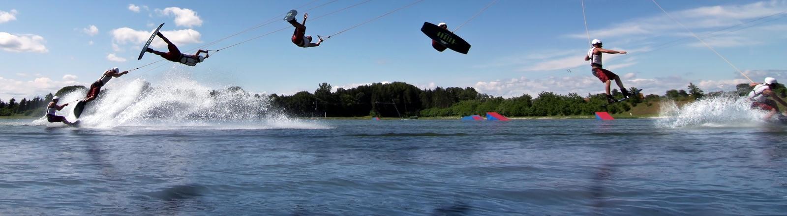 Ein Wakeboarder zeigt auf einem See seine Tricks.
