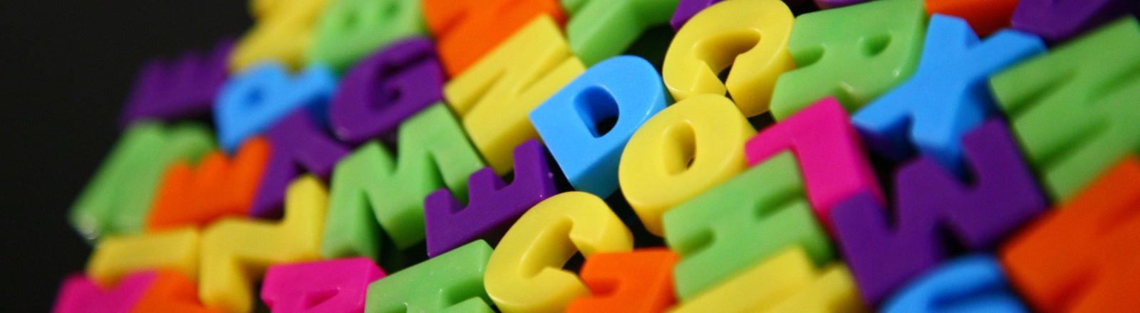 Viele bunte Spielzeugbuchstaben liegen auf einem Haufen.
