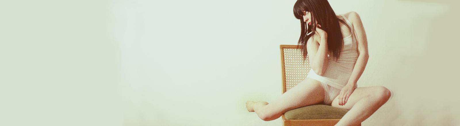 Eine Frau sitzt verdreht auf einem Stuhl.