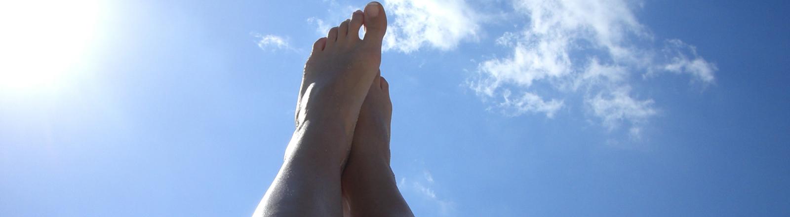 Nackte Beine werden in die Luft gestreckt