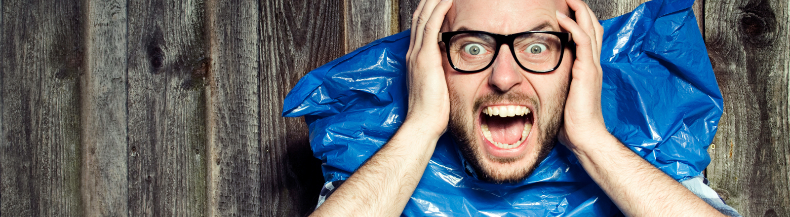 Ein Mann schreit vor Entsetzen. Und hat einen blauen Plastikmüllsack an.