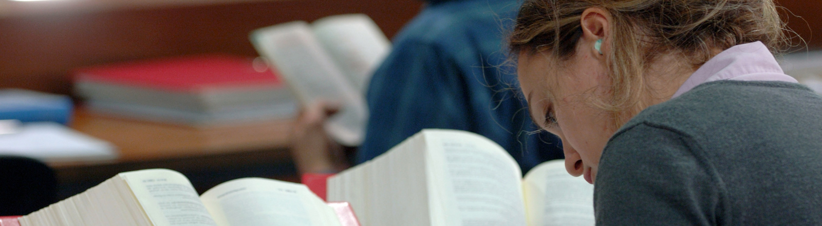Eine Studentin sitzt mit Lehrbüchern in Lesesaal der Kölner Universitätsbibliothek.
