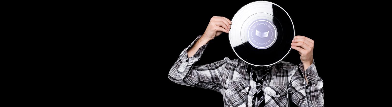 Ein Mann hält sich eine Schallplatte vor das Gesicht.
