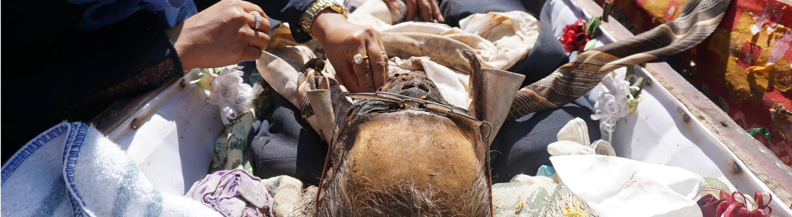 Die Angehörigen legen den frisch eingekleideten Toten wieder in den Sarg und legen im kostbare Grabbeilagen in den Sarg.