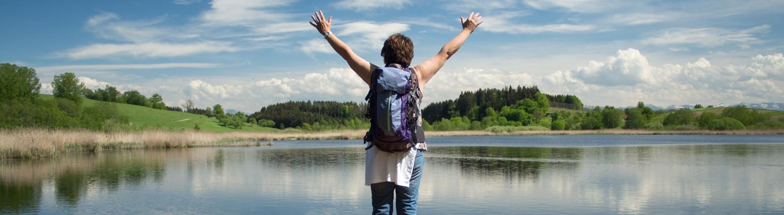 Eine Frau steht auf einem Steg an einem See und reckt die Arme in den blauen Himmel.