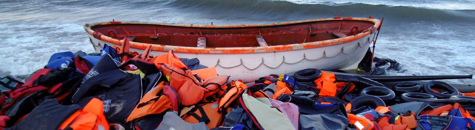 An einem Strand auf Lesbos liegt ein Boot, mit dem Flüchtlinge aus der Türkei übers Mittelmeer gekommen sind. Neben dem Boot haben sie ihre Rettungswesten zurückgelassen.