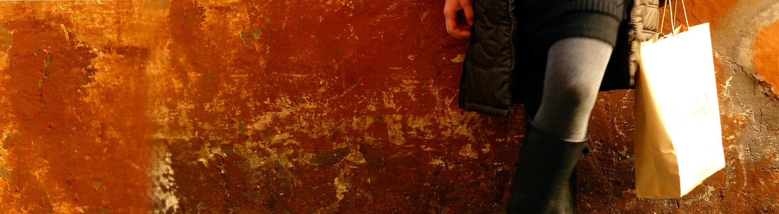 Ein Frau lehnt mit einer Papiertüte an einer roten Hauswand, wo der Putz abbröckelt.
