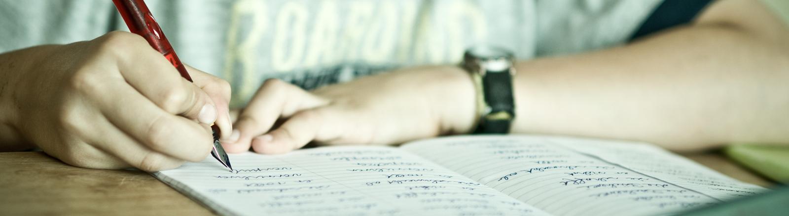 Schüler schreibt in ein Aufgabenheft.