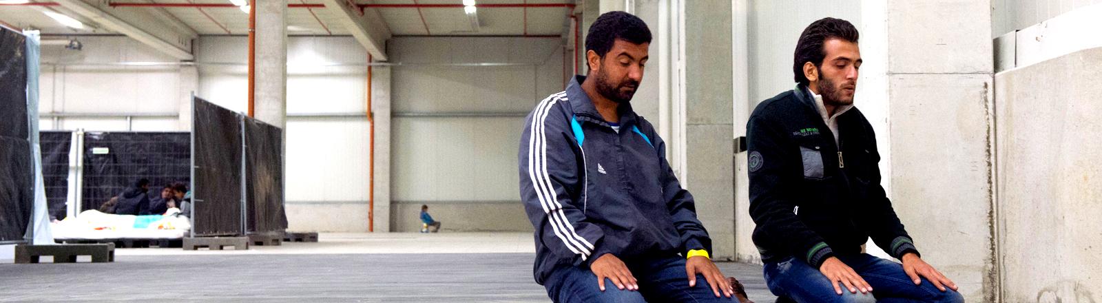 Zwei syrische Männer beten in einem vorrübergehenden Flüchtlingslager in Thüringen auf improvisierten Gebetsteppichen.