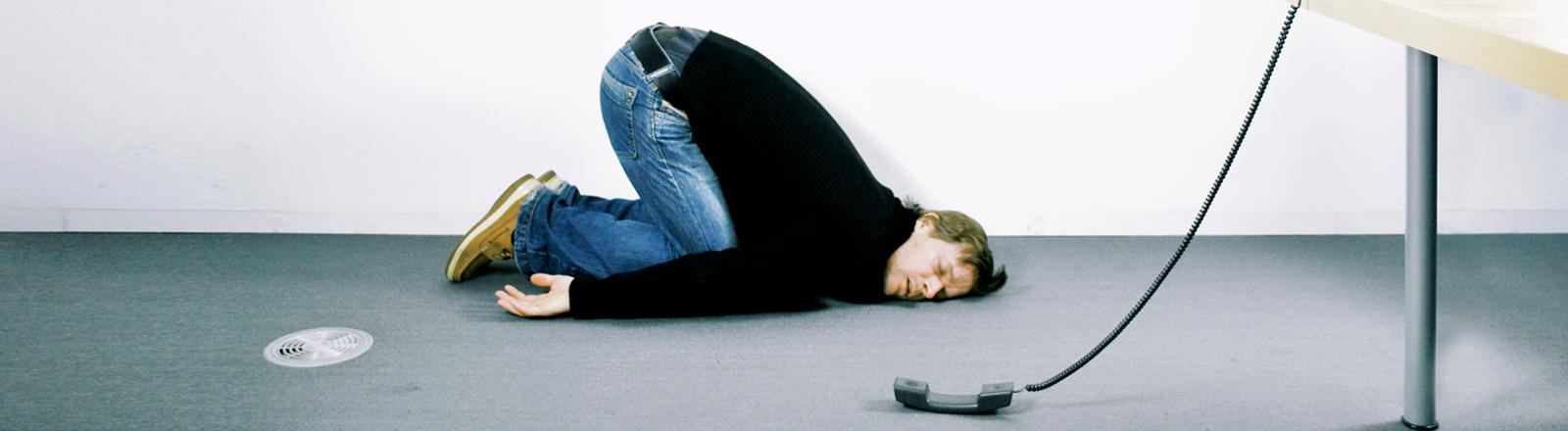 Ein Mann liegt erschöpft schlafend am Boden eines Büros. Neben ihm eine heruntergefallener Telefonhörer.