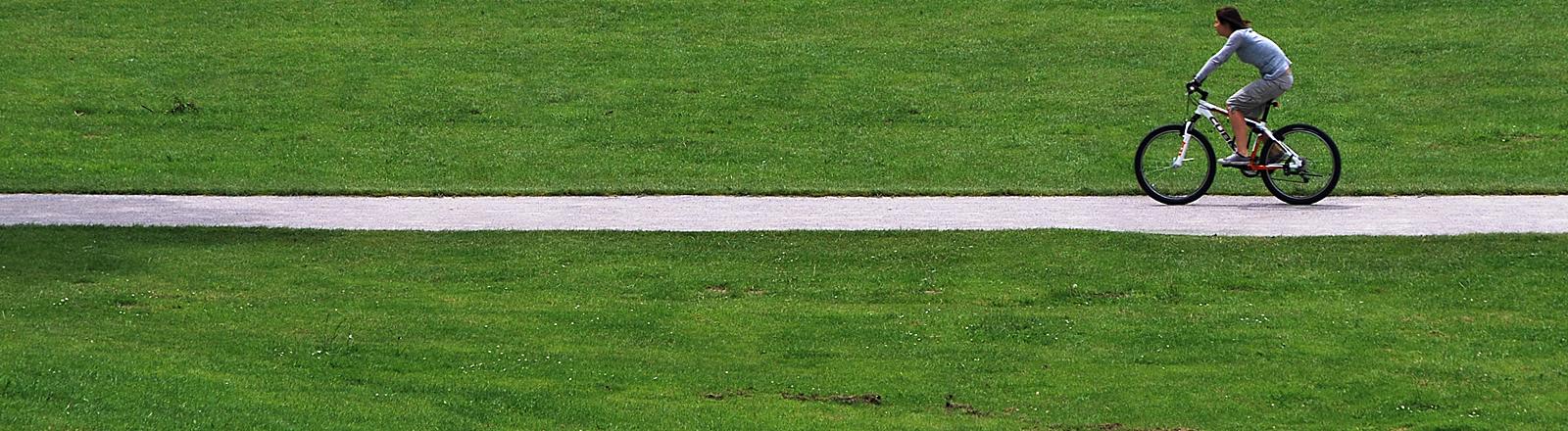 Eine Fahrradfahrerin fährt über einen Weg durch eine Wiese.