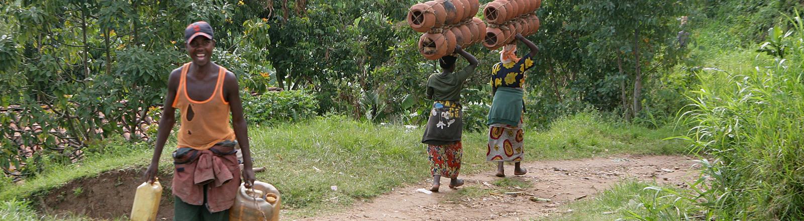 Ein junger ruandischer Mann transportiert mit Wasser gefüllte Plastikkanister, im Hintergrund sind zwei Frauen mit Tonkrügen zur Wasserstelle unterwegs, aufgenommen nahe Kigali am 02.11.2006.