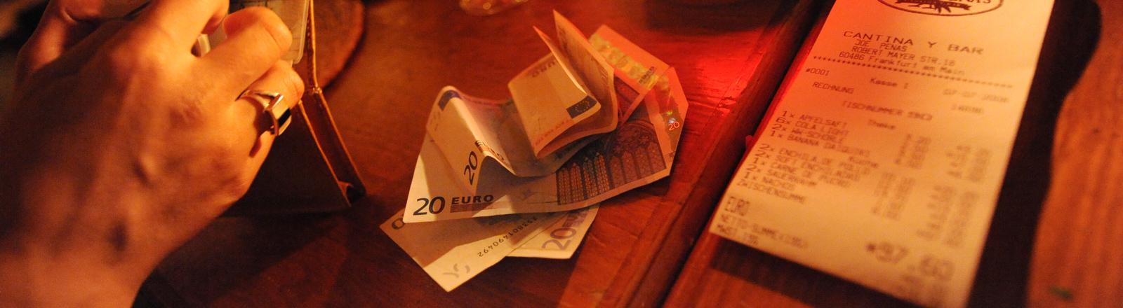Eine Frau bezahlt in einem Restaurant die Rechnung.