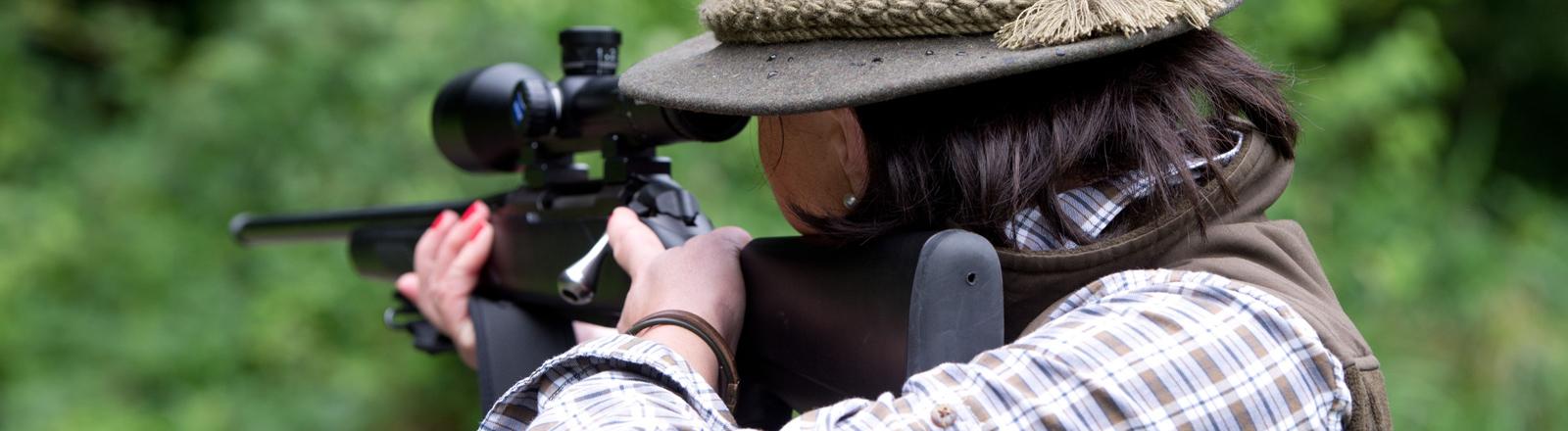 Jägerin zielt mit Gewehr.