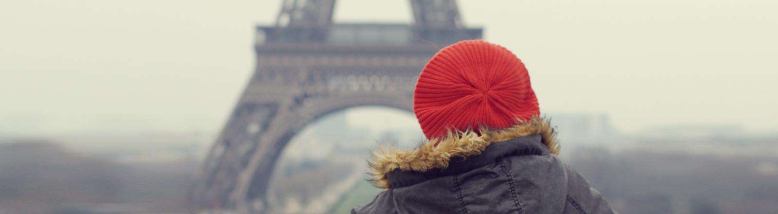Eine Frau schaut auf den Eifelturm in Paris.