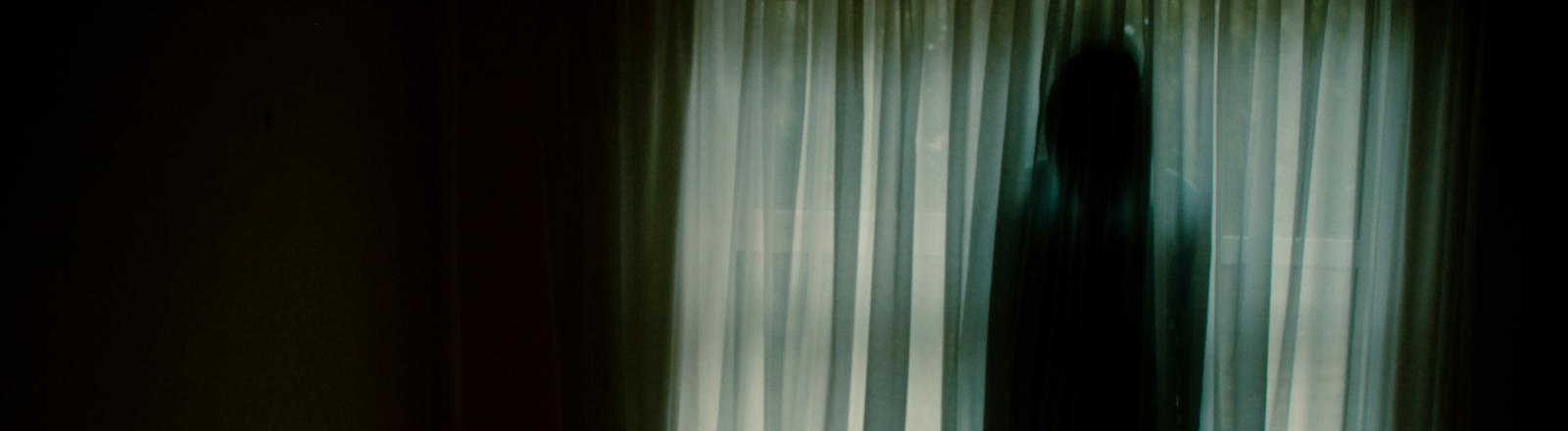 Eine Person steht im Dunkeln hinter einem Vorhang.