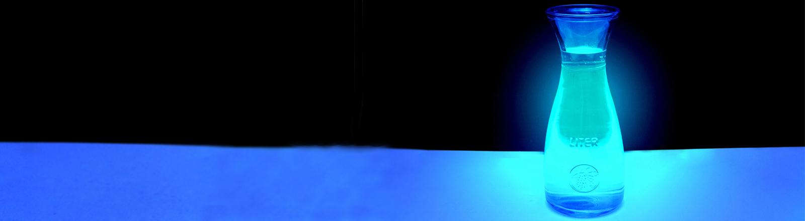 Eine Flasche mit weisslich-blau leuchtender Flüssigkeit vor schwarzem Hintergrund