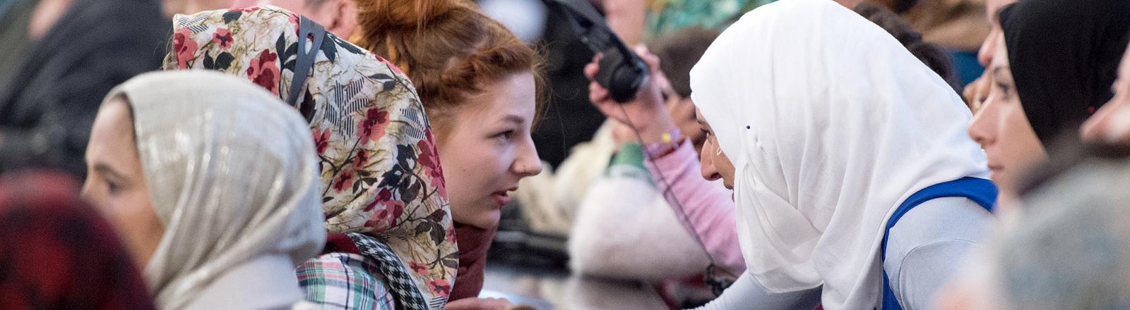 Eine Freiwillige und eine Flüchtlingsfrau unterhalten sich am 01.11.2015 in der Paulskirche in Frankfurt am Main (Hessen). Unter dem Motto «Frankfurt Hilft» veranstaltete die Stadt hier gemeinsam mit Flüchtlingen und Helfern ein Fest zum Dank an freiwillige und professionelle Helfer.