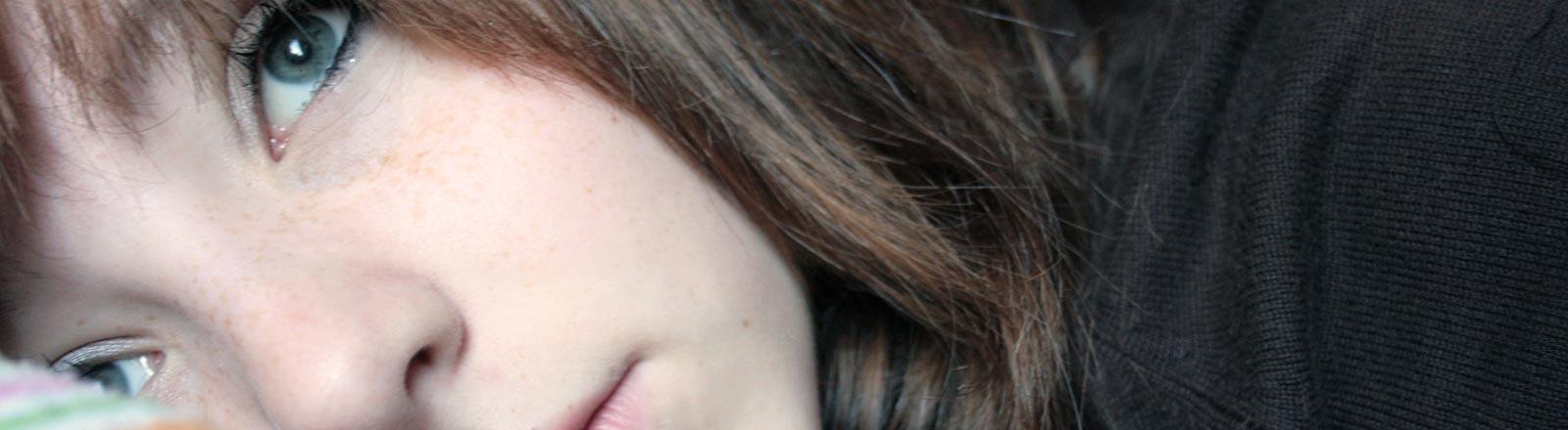 Eine junge Frau liegt auf dem Bett und schaut melancholisch in die Ferne.