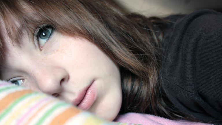 Eine junge Frau liegt auf dem Bett und blickt melancholisch in die Ferne.
