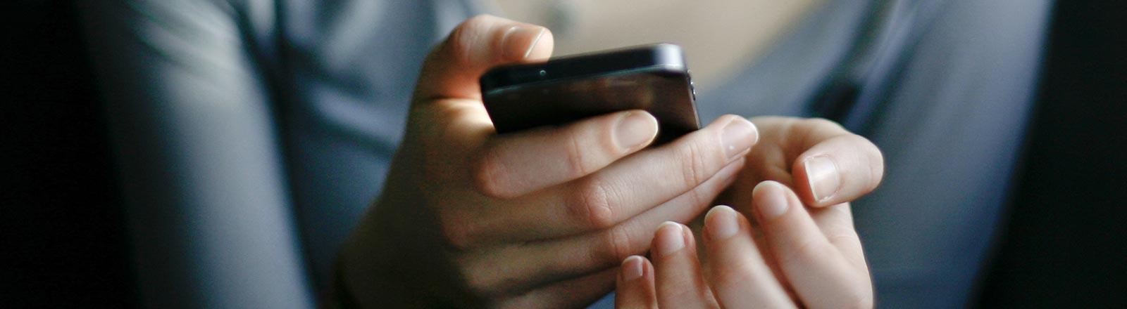 Eine Frau hält ein Mobiltelefon.