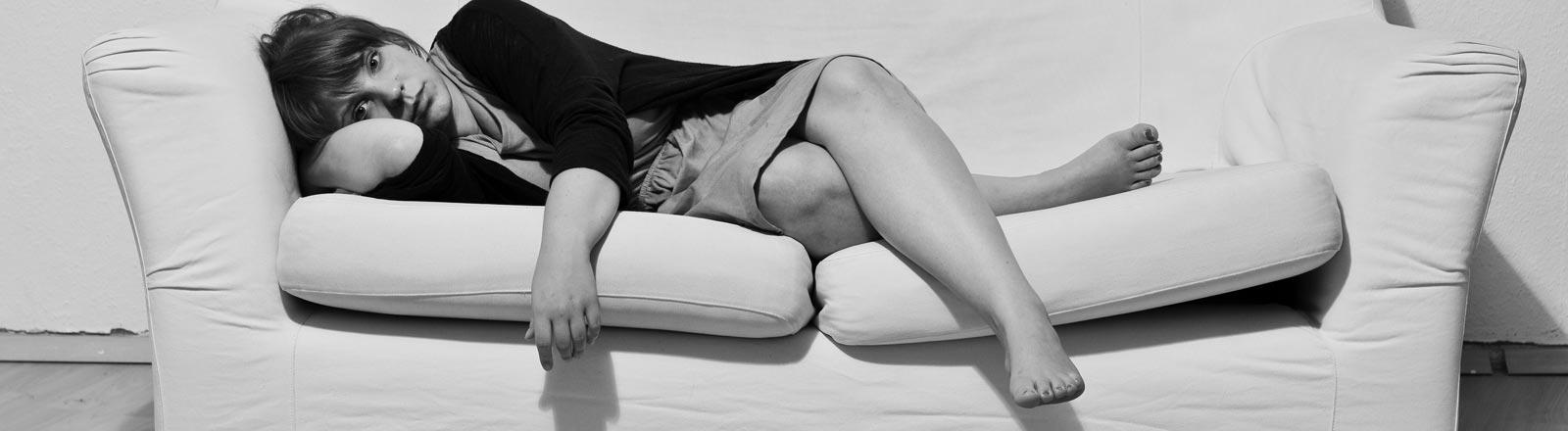 Eien Frau liegt auf einem Sofa.