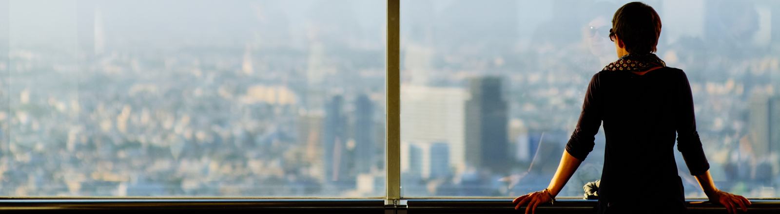Eine Frau blickt aus einem Hochhausfenster auf eine Großstadt.