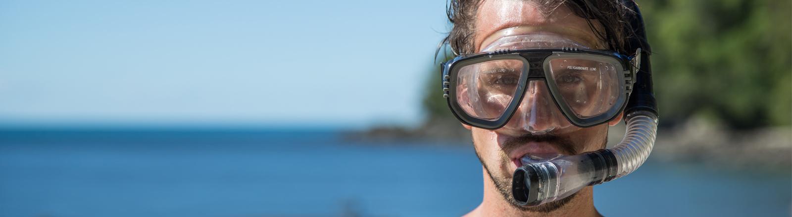 Ein Mann trägt eine Taucherbrille.