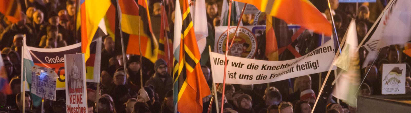 Die Anhänger des fremden- und islamfeindlichen Pegida-Bündnises demonstrieren am 25.01.2016 in Dresden (Sachsen) mit Fahnen und Transparenten.