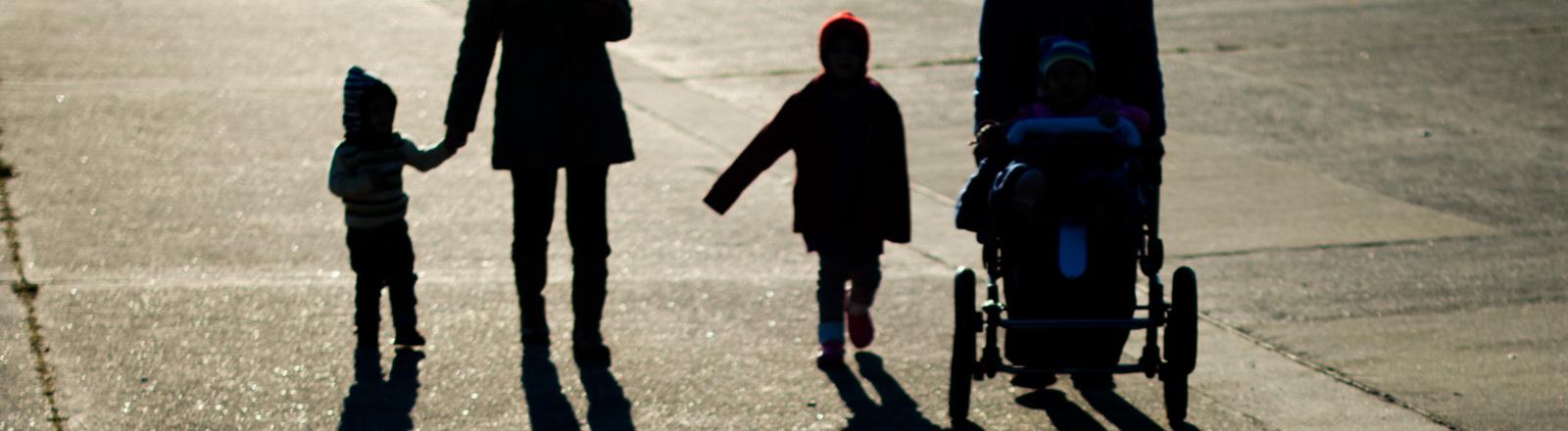 Flüchtlingsfamilie von hinten im Gegenlicht aufgenommen