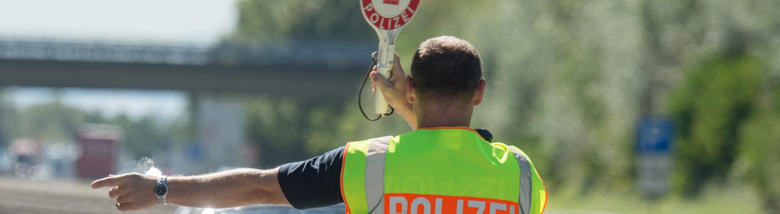 Ein Bundespolizist hält am 17.09.2015 an einer Kontrollstelle an der Autobahn A 3 kurz hinter der deutsch-österreichischen Grenze nahe Pocking (Bayern) ein Fahrzeug an.