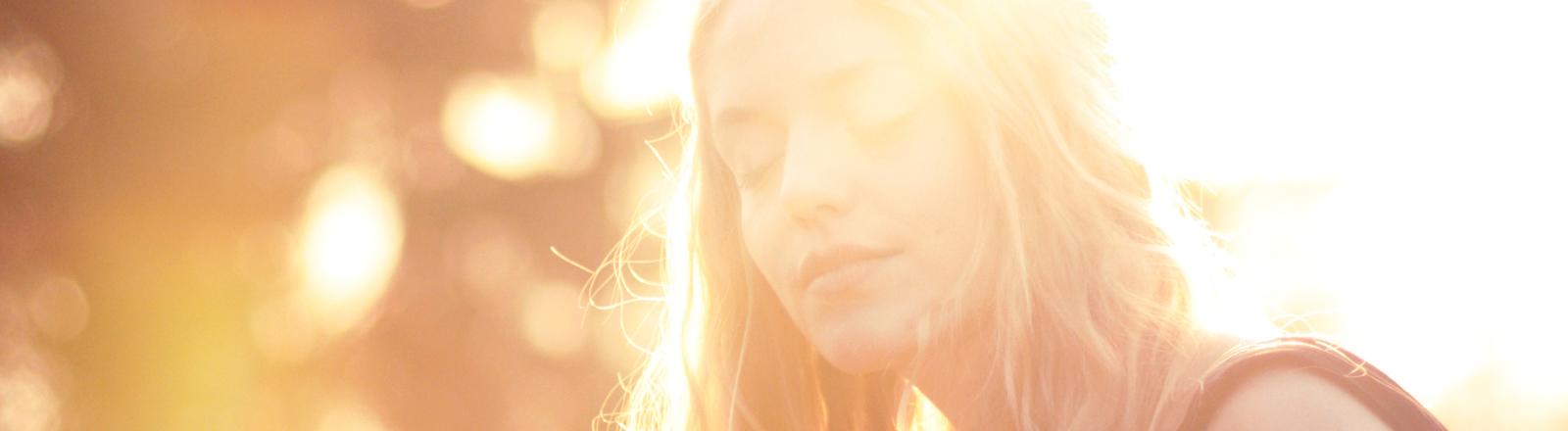 Eine Frau schließt verträumt die Augen, während sie in gleißenden Sonnenlicht sitzt.