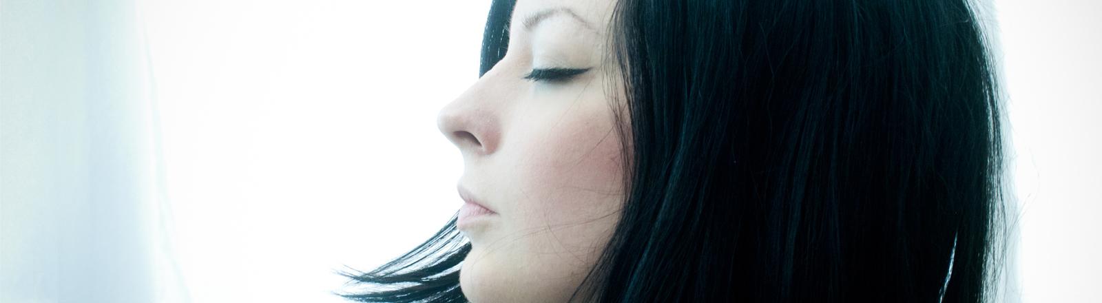 Eine Frau hat die Augen geschlossen.