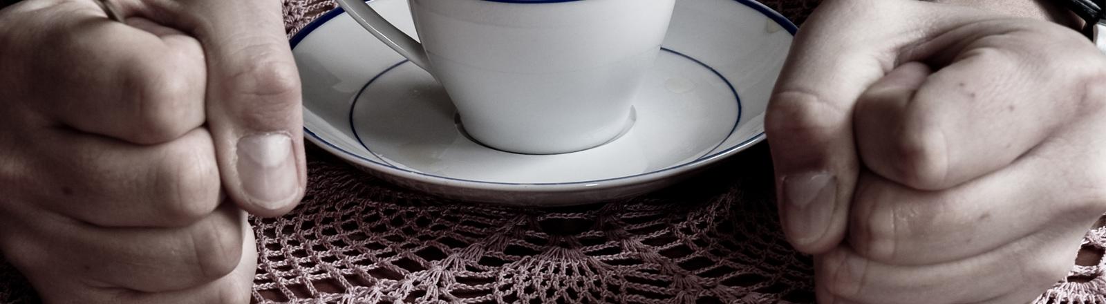 Kaffeetasse zwischen zwei geballte Fäusten auf dem Tisch