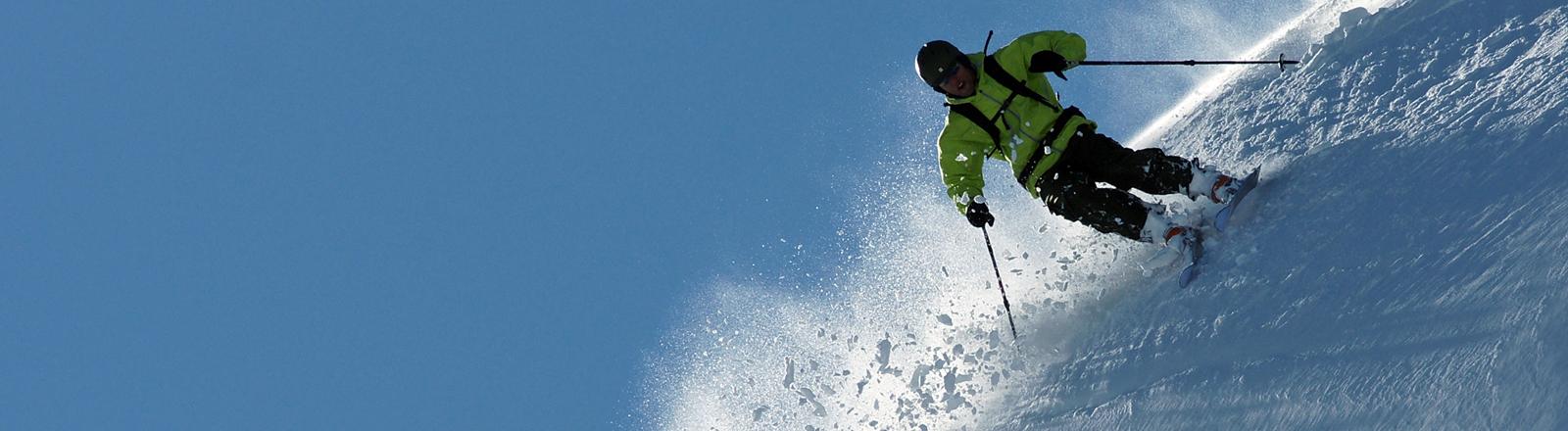 Ein Skifahrer braust die Piste herunter.