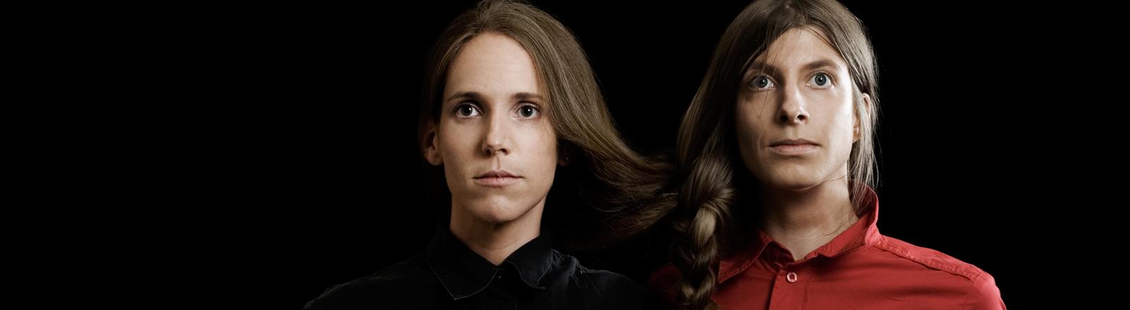 Zwillinge, Frauen stehen nebeneinander, sie haben ihre Haare zusammengebunden.