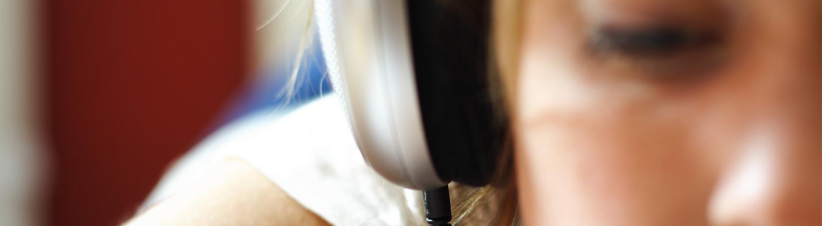 Frau trägt Kopfhörer und liest dabei.