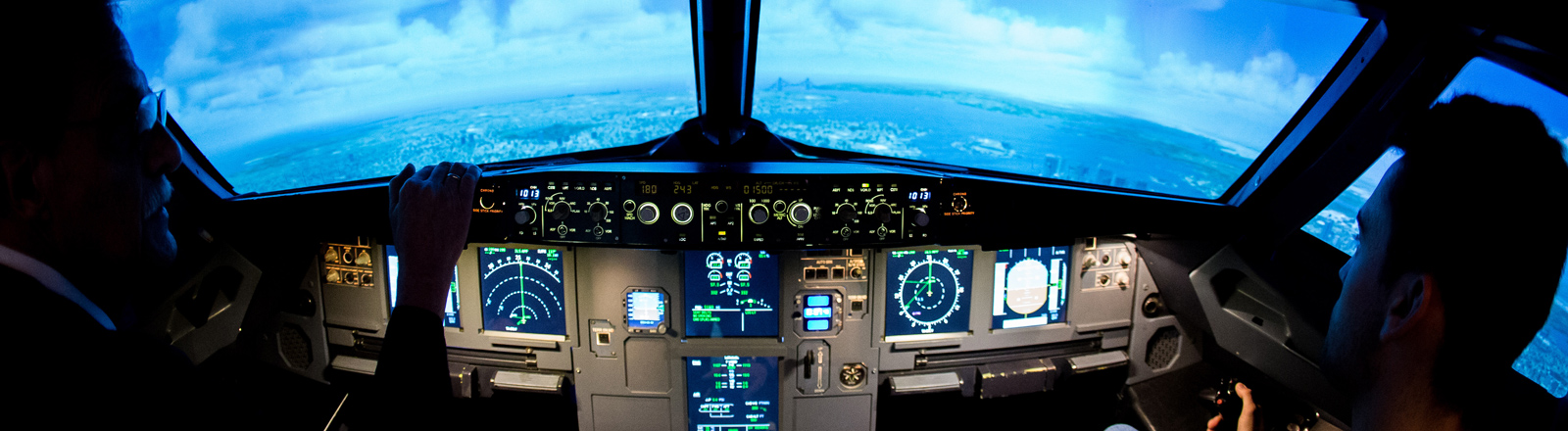 Zwei Männer sitzen im Cockpit eines Flugsimulators.